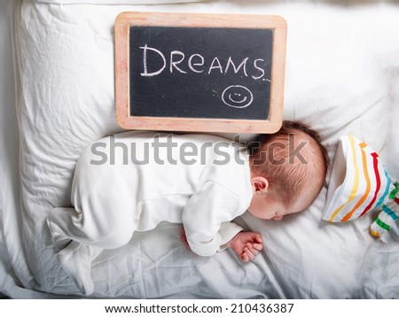 Caucasian newborn baby toddler boy sleeping in his bed with chalkboard signed dreams - stock photo