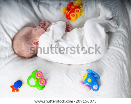 Caucasian newborn baby toddler boy sleeping in his bed with toys - stock photo