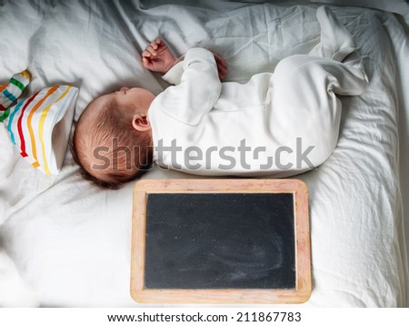 Caucasian newborn baby todler boy sleeping in his bed with blank chalkboard - stock photo