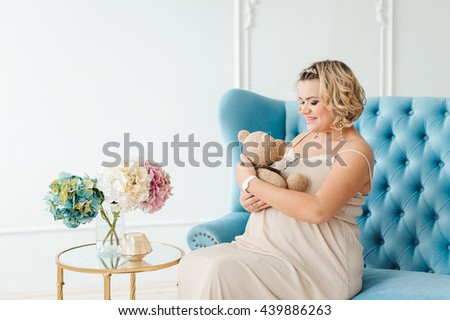 Caucasian pregnant woman sitting on the blue sofa on a white background and holding a teddy bear - stock photo