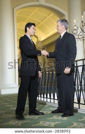Caucasian prime adult male businessman and Asian prime adult male businessman in hotel. - stock photo