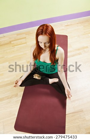 Caucasian redhead woman in green shirt at lotus position meditation above view - stock photo