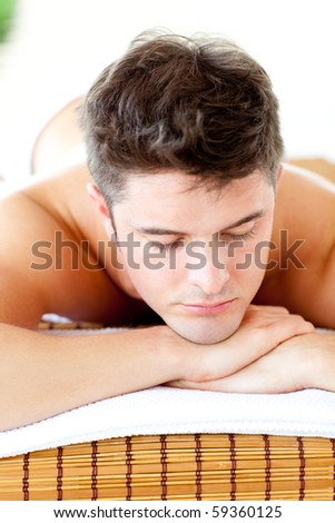 Caucasian relaxed young man lying on a massage table in a spa center - stock photo