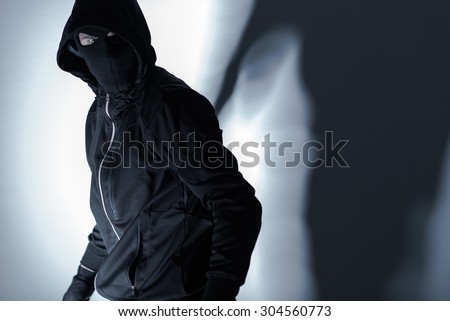 Caucasian Robber in Black Mask and Black Gloves Preparing for Robbery. - stock photo