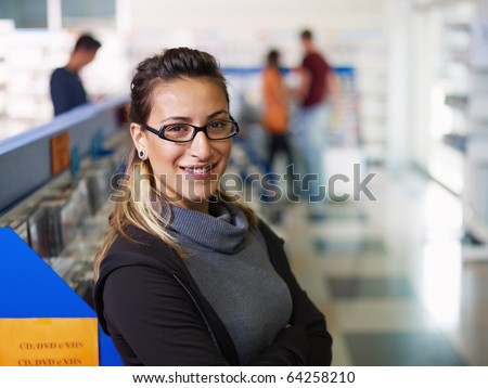 caucasian salesclerk looking at camera with arms folded in music shop, with customers in background. Horizontal shape, front view, waist up, copy space - stock photo