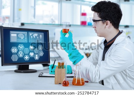 Caucasian scientist doing experiment while writing the observation result on the clipboard - stock photo