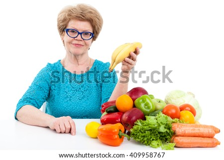 Caucasian senior woman showing ripe bananas in hand while sitting near fresh fruit and vegetables, isolated on white background - stock photo