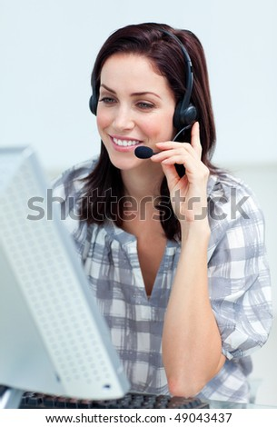 Caucasian smiling businesswoman with headset on working at a computer - stock photo