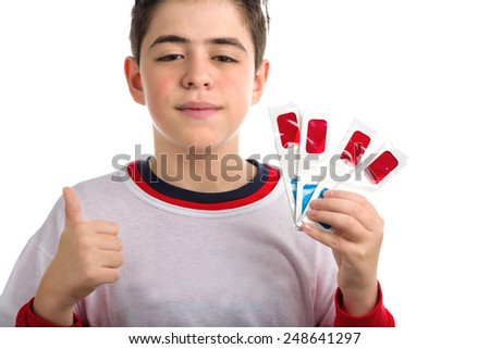 Caucasian smooth-skinned boy looks calm and confident and holds four 3D Cinema paper eyeglasses with red and sky-blue lenses with left hand while making success sign with right hand - stock photo