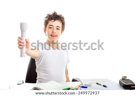 Caucasian smooth-skinned boy smiles holding 3D print labelled flashlight with right hand while doing  homework - stock photo