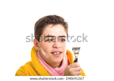 Caucasian smooth-skinned boy wears a yellow bathrobe with a pink towel around his neck: he has some patches on his face and smiling stares with crossed eyes at the razor he used for shaving - stock photo