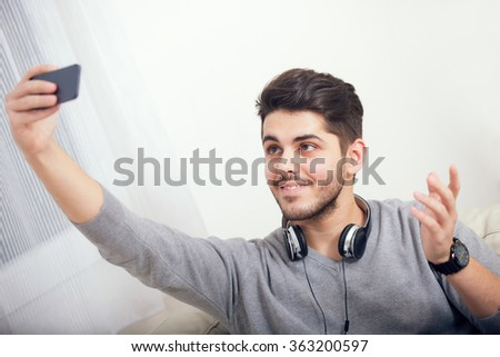 Caucasian student aged male taking a selfie with his phone at home - stock photo