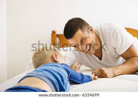 Caucasian toddler boy and father playing in bed. - stock photo