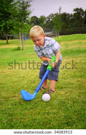 Caucasian toddler playing at park with toy golf club - stock photo