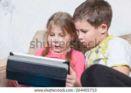 Caucasian two kids having fun with tablet pc while sitting on sofa - stock photo
