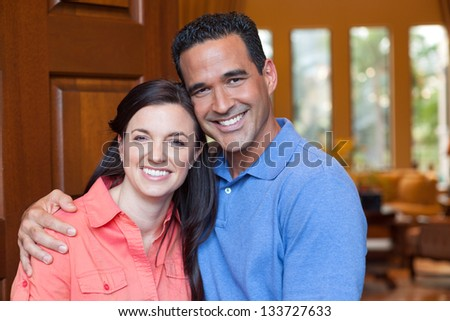 Caucasian wife and hispanic husband standing in entryway of home with tall wooden door, and windows, high ceilings, smiling during day. - stock photo