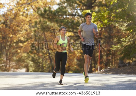 Caucasian woman and man jogging on a country road - stock photo