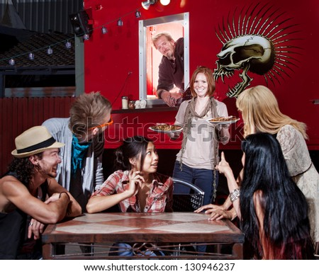 Caucasian woman bringing pizza orders to friends from canteen - stock photo