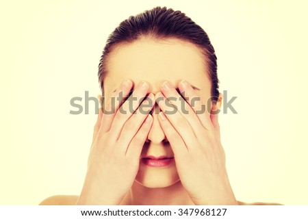 Caucasian woman covering her eyes. - stock photo