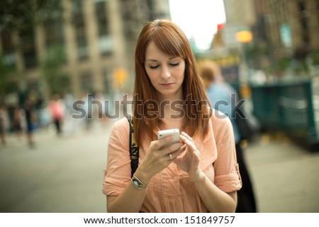 Caucasian woman female using iphone cellphone smartphone walking streets New York City - stock photo