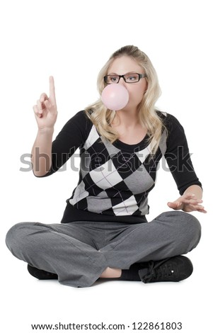 Caucasian woman gesturing her finger while blowing a bubble gum - stock photo