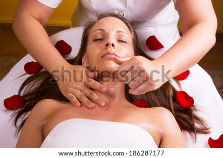 Caucasian woman get massage in a spa bed with flower. - stock photo