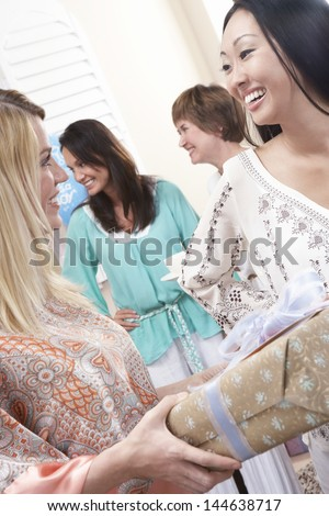 Caucasian woman giving a gift to pregnant Asian female at baby shower - stock photo