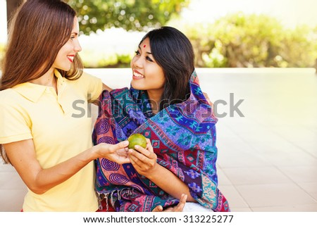 caucasian woman giving food to poor indian woman - stock photo
