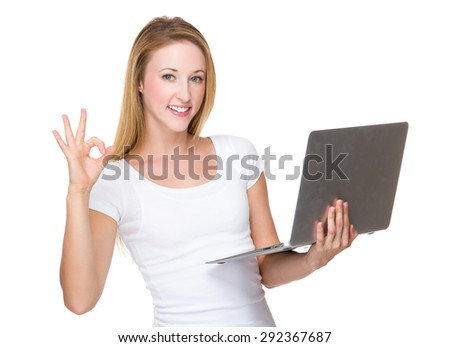 Caucasian woman hold with laptop computer and ok sign gesture - stock photo