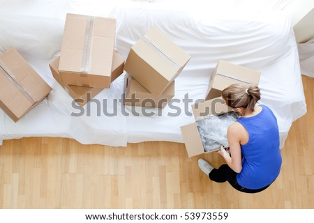 Caucasian woman holding a box at home - stock photo