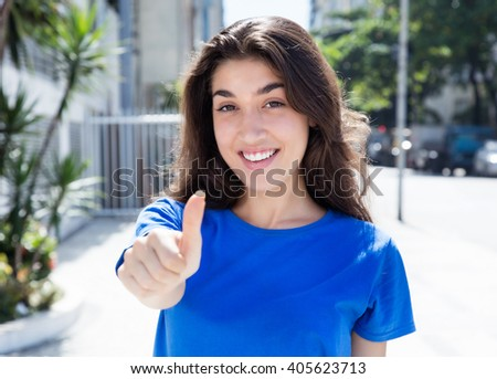 Caucasian woman in a blue shirt showing thumb up - stock photo