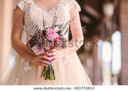 caucasian woman in beige wedding dress hold a bouquet of pink and purple flowers with lavender - stock photo