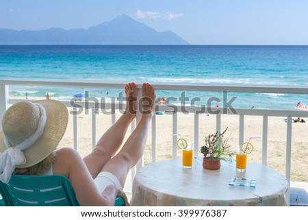 Caucasian woman in vintage hat sitting and relaxing on balcony of the hotel with idyllic sea scenery, looking at sea and holy mountain Athos in background. - stock photo