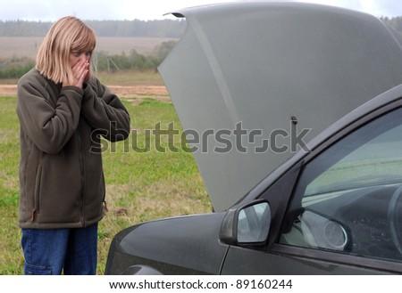 Caucasian woman is looking at the motor of her broken car in despair - stock photo