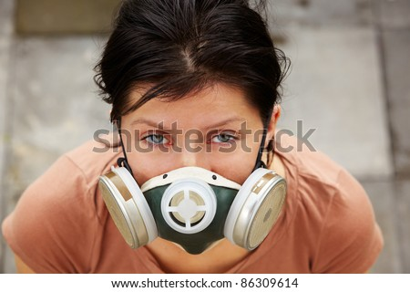 caucasian woman is wearing a gas mask - stock photo