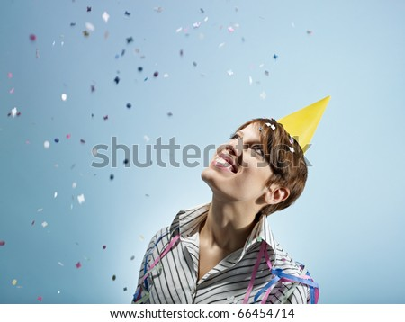 caucasian woman looking at confetti in the air. Horizontal shape, side view, head and shoulders, copy space - stock photo
