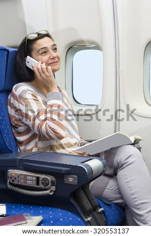 caucasian woman passenger in airplane using mobile  smart device and  reading a book  in comfortable flight and trip - stock photo