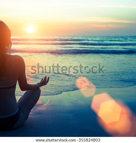 Caucasian woman practicing yoga at seashore during sunset. - stock photo