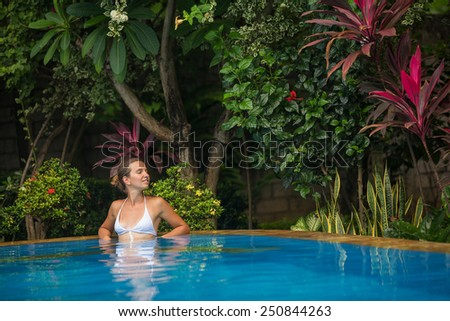 Caucasian woman rests at pool - stock photo