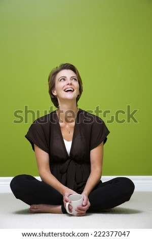 caucasian woman sitting in the green room holding cup of coffee - stock photo