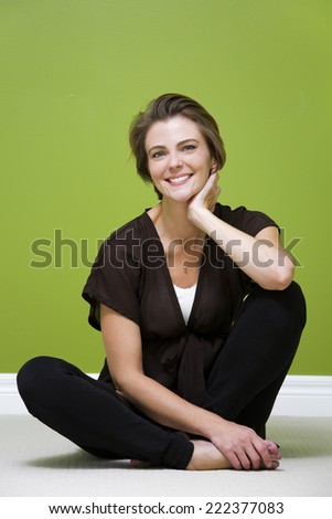 caucasian woman sitting in the green room relaxing - stock photo
