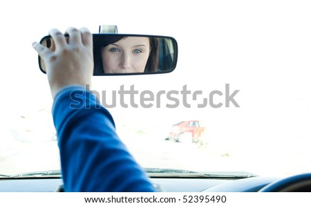 Caucasian woman sitting on driver's seat and looking in the rear-view mirror - stock photo