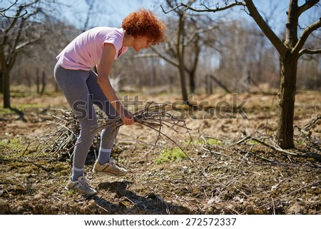 Caucasian woman spring cleaning the orchard, gathering cut branches to throw them away - stock photo