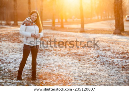 Caucasian woman standing in the park in sunlight of sunset sun, copyspace - stock photo