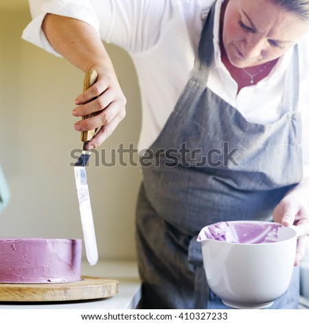 caucasian woman trimming the cream icing on a lilac cake with a spatula - stock photo