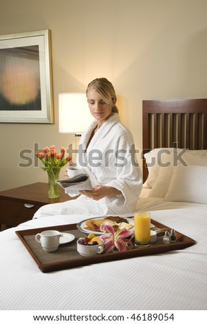 Caucasian woman wearing a bathrobe sits on a hotel bed with tray of breakfast. She is reading a newspaper and holding a coffee cup. Vertical format. - stock photo
