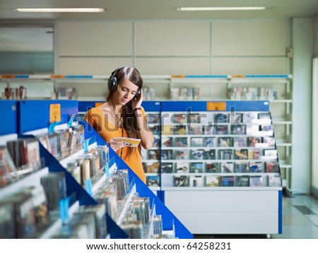 caucasian woman with headphones, choosing cd in music shop. Horizontal shape, front view, waist up, copy space - stock photo