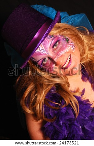 Caucasian woman with Mardi Gras mask painted on her face - stock photo