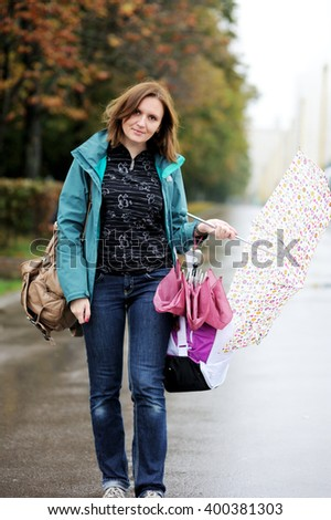 Caucasian woman with umbrella  in casual clothes in the rain on city street - stock photo