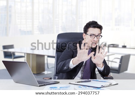Caucasian worker with scared expression working in the office laptop and business document on the table - stock photo
